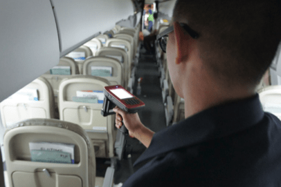Airline worker using RFID scanner inside plane